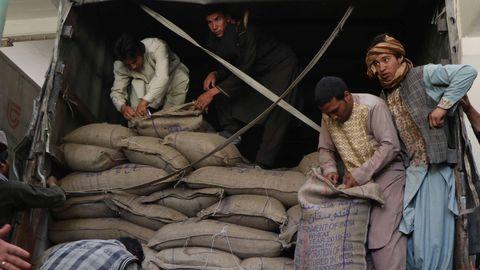 Trabajadores afganos descargan sacos de trigo, proporcionados por la India, en Herat