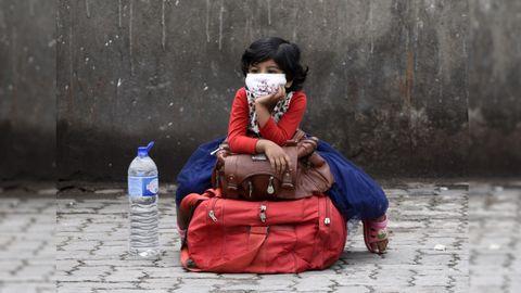 Una niña espera en una parada de autobús de la ciudad india de Guwahati
