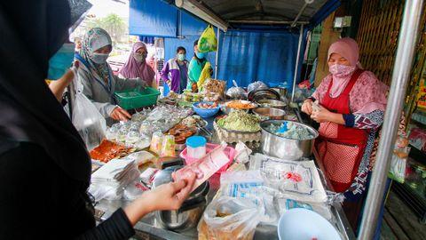 En Tailandia las mujeres acuden a los mercados vistiendo mascarillas
