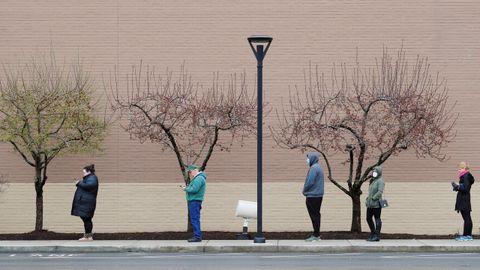 Las personas respetan el distanciamiento social en el acceso a una tienda en Massachusetts