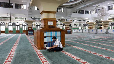 Un guardia de seguridad lee el Corán en una mezquita vacía durante el Ramadán en Bangladesh
