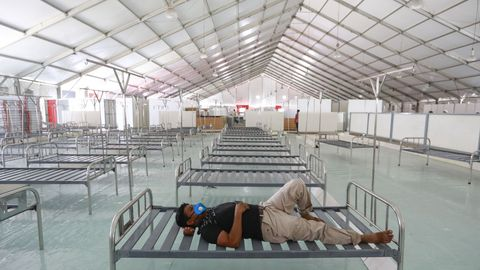En Dacca, un trabajador descansa durante la instalación de un nuevo hospital de campaña