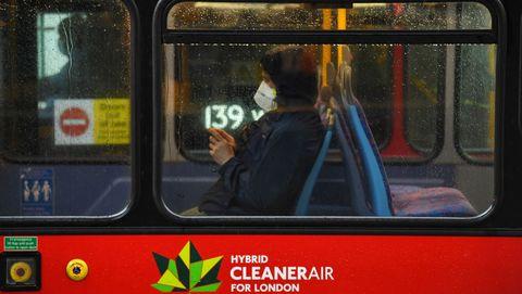 Una mujer lleva una máscara facial en un autobús londinense