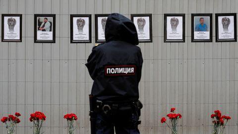 Un policía observa un monumento improvisado en honor a los médicos en San Petersburgo