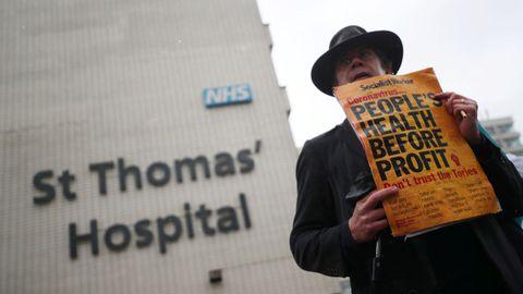 Un hombre sostiene un cartel de protesta ante un hospital londinense