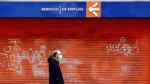 Un hombre ataviado con una máscara sanitaria pasa frente a una oficina pública de empleo cerrada, en Oviedo.