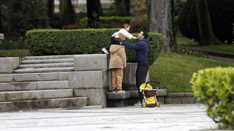 Un hombre juega con sus hijas en un parque del centro de Oviedo