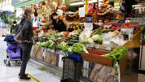 Varias personas realizan sus compras en una frutería en la plaza del Fontán de Oviedo