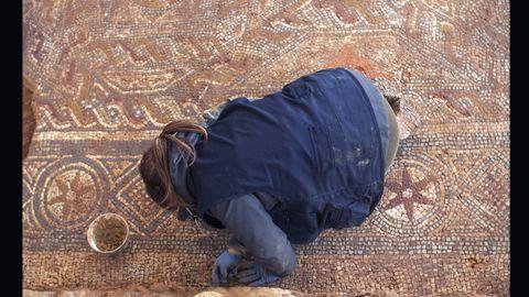 La restauradora Mónica Ruiz trabaja en un lateral del pavimento retirando materiales