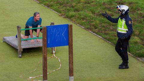 Un policia informa a un hombre de la prohibicion de hacer deporte en algunas zonas del parque de Invierno en Oviedo