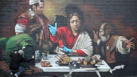 El artista Lionel Stanhope pinta un mural en Londres que representa la Cena de Emaús, de Caravaggio, con guantes protectores