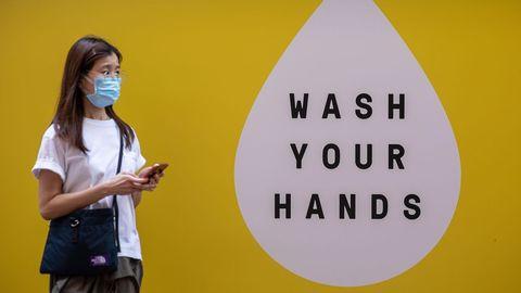 En Hong Kong, una mujer pasa por delante de un mural que anima a lavarse las manos