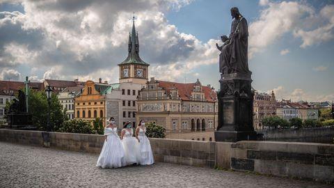 Tres modelos posan vestidas de novia en el puente de Carlos, en Praga, ataviadas con mascarillas