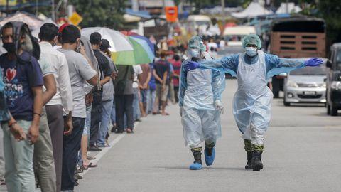 En Malasia, un sanitario pide a las personas que aguardan para recibir protecciones que mantengan la distancia de seguridad