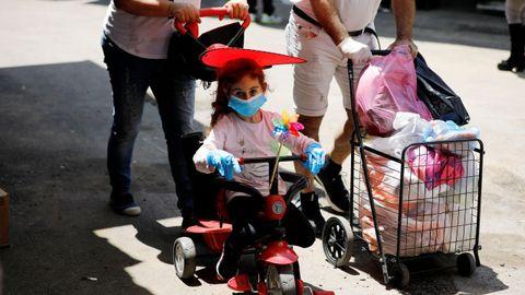 Una niña pasea con mascarilla y guantes cerca del mercado del Carmel, en Tel Aviv
