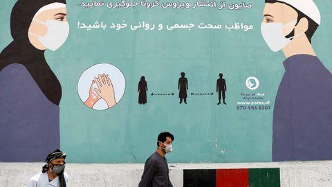 Un hombre afgano con una máscara facial protectora pasa junto a una pared pintada que advierte sobre el covid-19