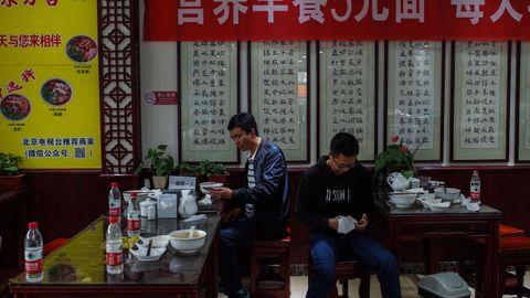 Dos clientes comen en un restaurante en China, el país donde se originó la pandemia
