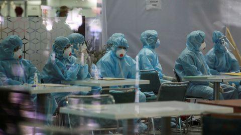 Médicos con trajes de protección se preparan para examinar a pasajeros que llegan al aeropuerto de Nueva Dehli