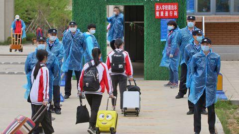En la localidad china de Yantai los estudiantes han regresado a las aulas. Los policías supervisan su entrada con mascarillas y batas plásticas