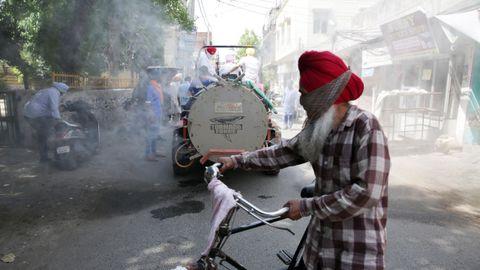 Un trabajador rocía desinfectante en una calle de la localidad india de Amritsar, ante la mirada de los transeúntes