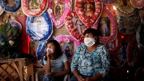 Una mujer y su hija aguardan la llegada de clientes en una tienda de Ciudad Juárez en la que venden objetos religiosos
