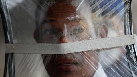 Zaul Ortega, de 53 años, se cubre el rostro con una bolsa plástico mientras hace fila para comprar en un supermercado en Ciudad de Panamá