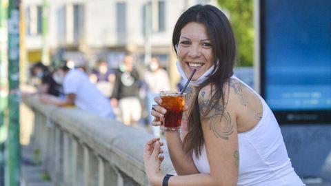 Una joven toma un aperitivo en la dársena de Milán