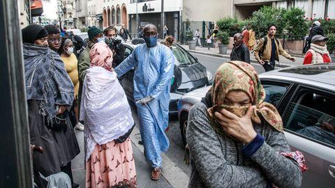 Habitantes del popular barrio parisino de la 'Goutte d'Or  fuera de una tienda de ropa mientras los empleados distribuyen mascarillas