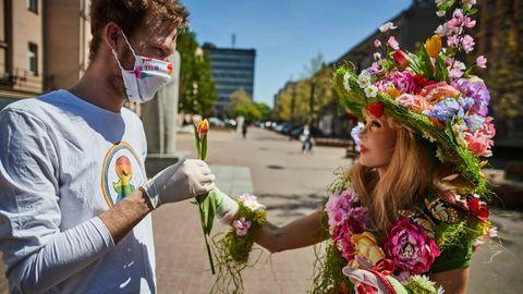 Una mujer vestida de flores entrega una a un joven con mascarilla en Lodz, Polonia