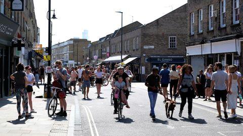 La gente pasea y va en bicicleta por Broadway Market, en Londres
