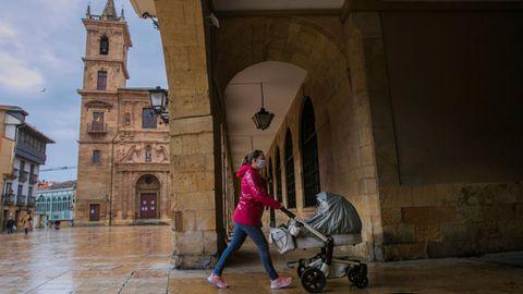 Una mujer ataviada con una mascarilla pasea a su hija recién nacida en la plaza del ayuntamiento de Oviedo