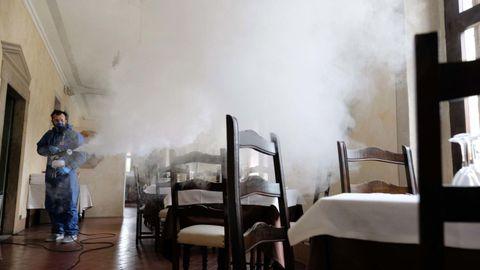 Un trabajador desinfecta el restaurante de Olimpo en Brescia, Italia