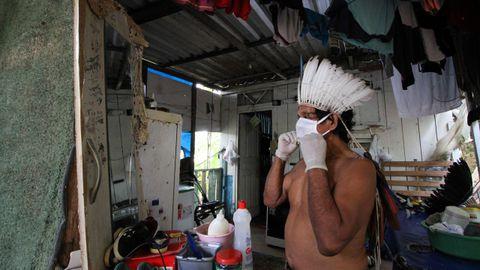 En Manaos, Brasil, un indígena se prueba ante el espejo una mascarilla protectora