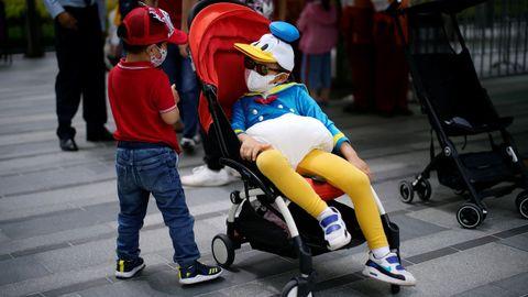 En Shanghai hoy ha reabierto el parque de atracciones de Disneyland. Lo usuarios acuden con mascarilla