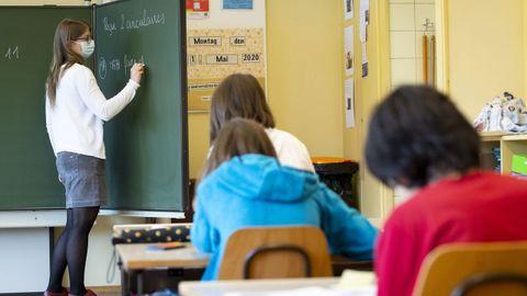 Una profesora, con mascarilla, imparte hoy clase a alumnos de primaria en Morges (Suiza)