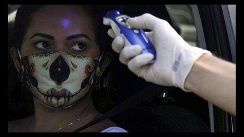 Un sanitario toma la temperatura a una mujer en Brasil