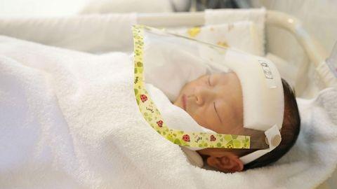 Un bebé recién nacido, con pantalla protectora en un hospital de Tokio