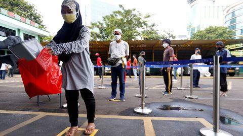 En Indonesia practican el distanciamiento social también cuando acuden a los dispensadores de arroz