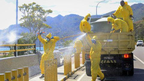 En Timor Oriental un grupo de trabajadores rocía desinfectante para combatir la pandemia