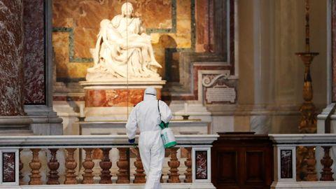 Un trabajador desinfecta ante la Piedad de Miguel Ángel, en la basílica de San Pedro del Vaticano