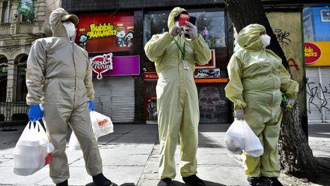 En la capital de Bolivia, La Paz, hombres enfundados en trajes de protección esperan en la calle tras hacer la compra