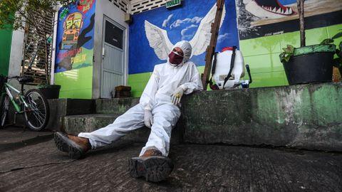En Bandung, Indonesia, un operario con un traje protector se toma un respiro en las tareas de desinfección