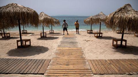 Trabajadores instalan pasillos de madera en una playa de Atenas que reabrirá este sábado