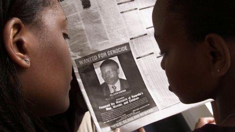 Unas mujeres observan un anuncio con la recompensa de cinco millones de dólares que ofrecia EE.UU. por Kabuga