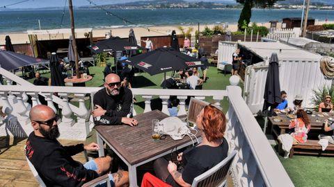 Gente disfrutando en las terrazas de la playa de Gandarío