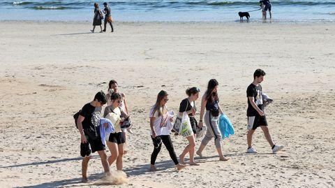 Algunos jóvenes aprovecharon para acercarse al arenal de playa América (Panxón)