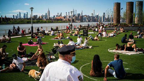 La Policía de Nueva York supervisa que se mantenga el distanciamiento social en Domino Park, donde han pintado círculos sobre el césped