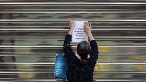Una mujer coloca un aviso en la persiana cerrada de un negocio del centro de Oviedo, durante el estado de alarma