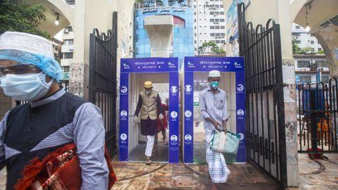 Musulmanes pasan a través de una cámara de desinfección para acceder a una mezquita en Dacca