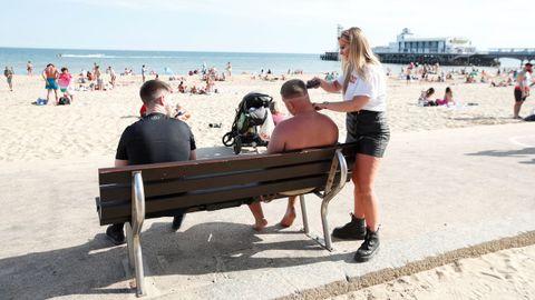 En la playa británica de Bournemouth impera la distancia social, aunque también se dan escenas curiosas como un corte de pelo a pie de arenal